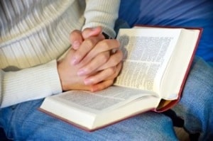 folded hands with bible